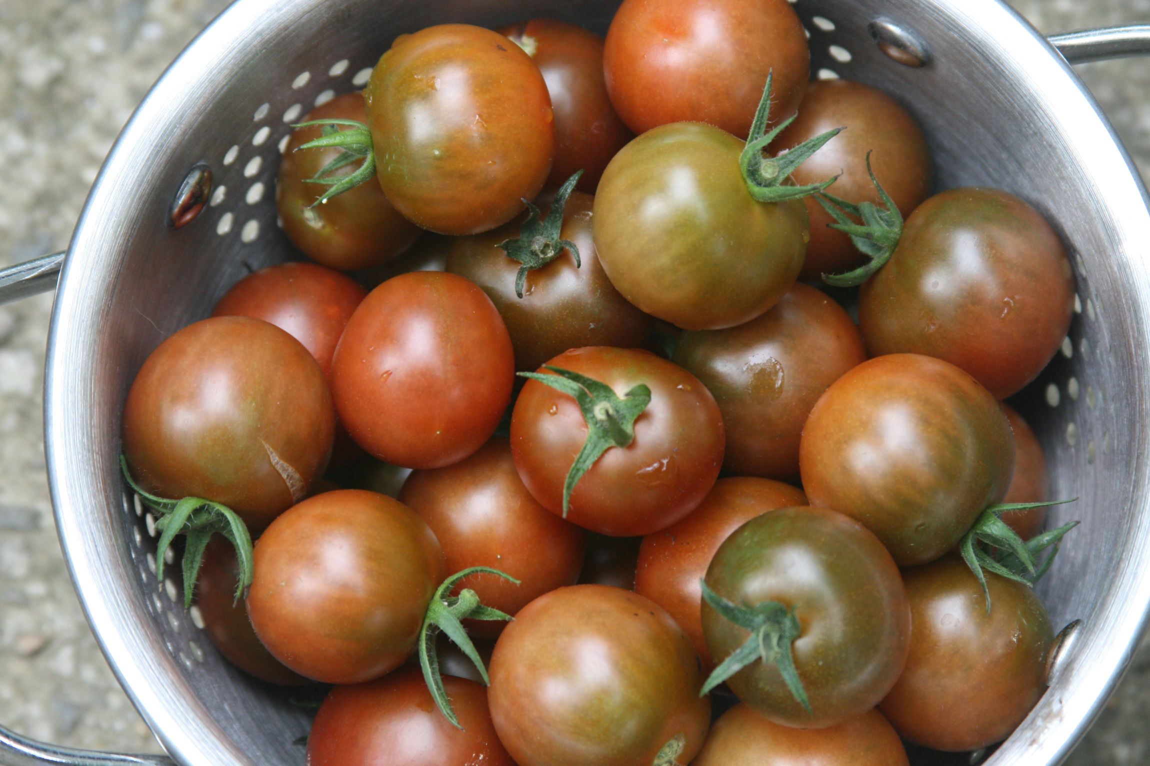 Cherry tomatoes in a metal colander.
