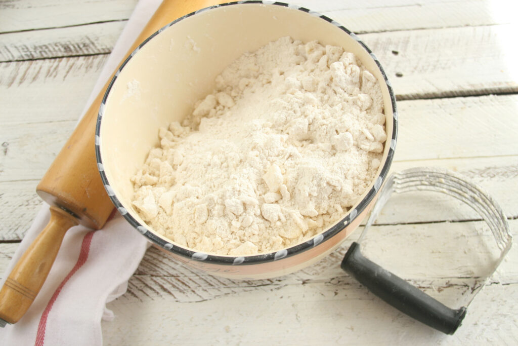 large mixing bowl with flour and pea size pieces of butter and lard making pie dough