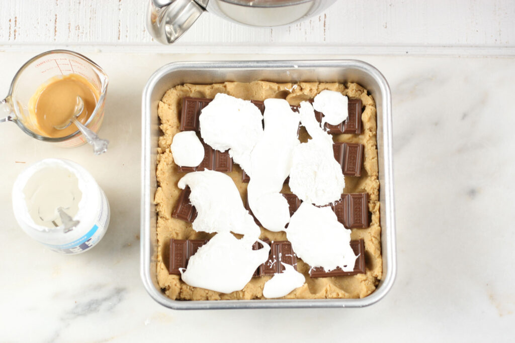 Layering s'more bars in a 8x8-inch baking pan with fluff and chocolate bar