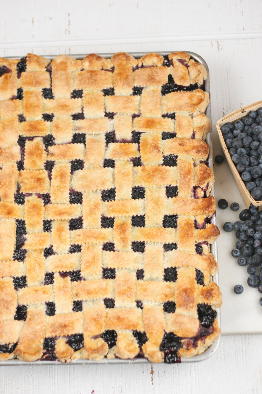 blueberry pie on a half sheet pan with homemade crust.