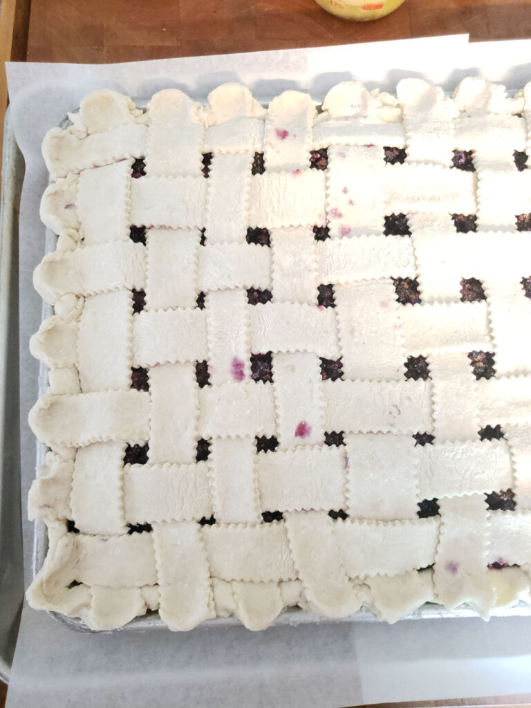 Pie with lattice crust unbaked on a half sheet pan