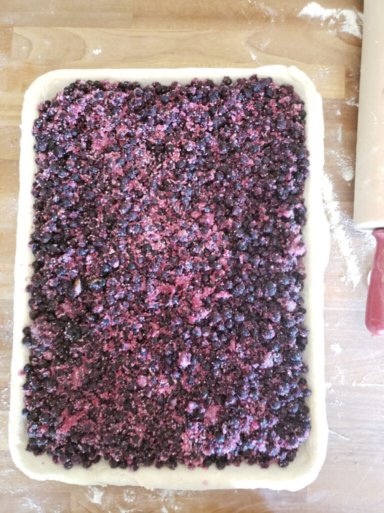 blueberry pie without the top crust on a half sheet pan