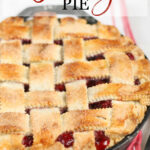 Cherry pie with lattice weaved crust in dual handle cast iron skillet on white marble.