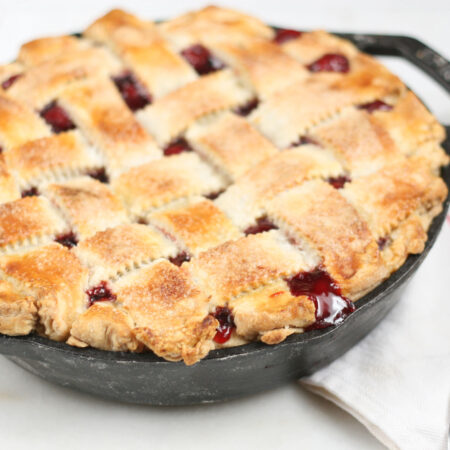 homemade cherry pie with lattice crust in a 2-handle cast iron skillet