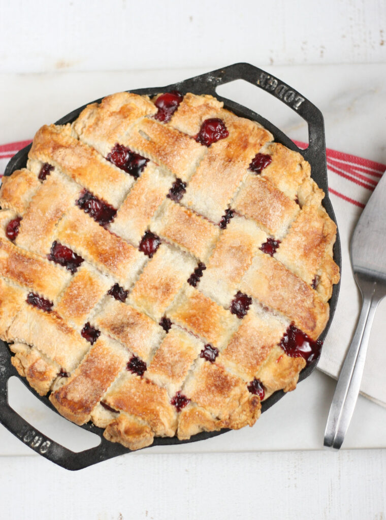 homemade cherry pie with a lattice crust in a 2-handle cast iron pan