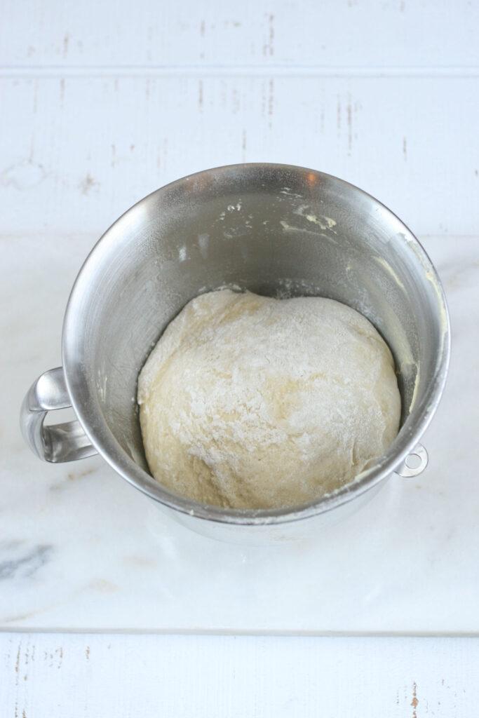 Pizza dough rising in mixing bowl