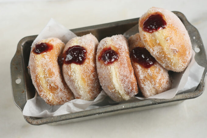 Homemade Jelly donuts lined up against each other in a metal loaf pan lined with white parchment paper