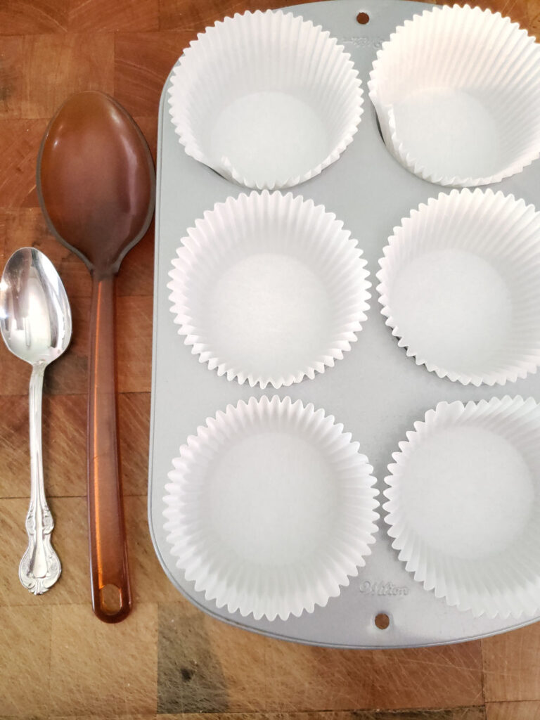 Jumbo cupcake pan lined with paper liners and spoons to the left of the pan