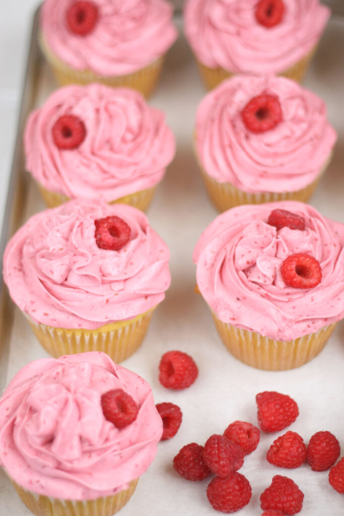 cupcakes with raspberry frosting lined up on a sheet pan