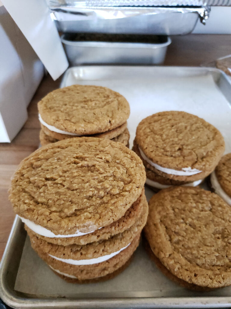 Oatmeal creme pies stacked on a half sheet pan