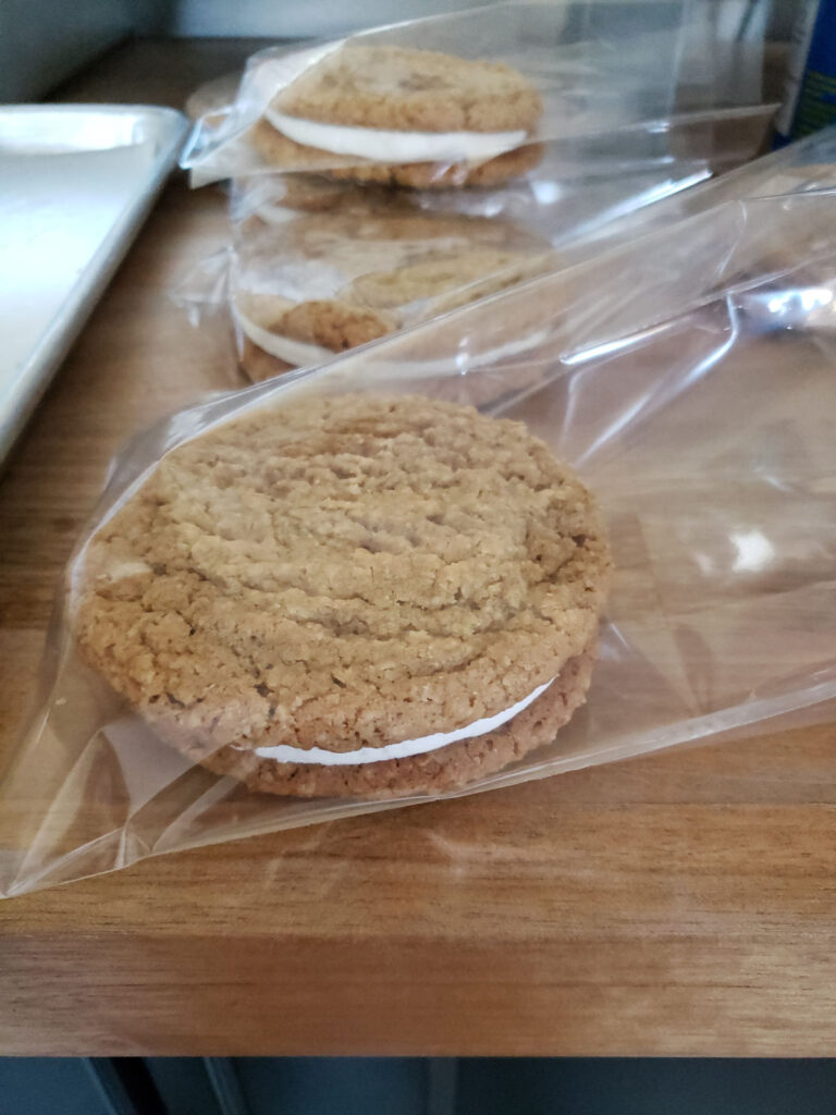 oatmeal sandwich cookies in plastic baggies on a butcher block