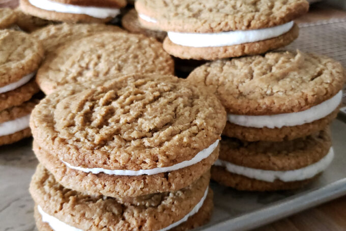 Oatmeal cream pies stacked on top of each other on a sheet pan