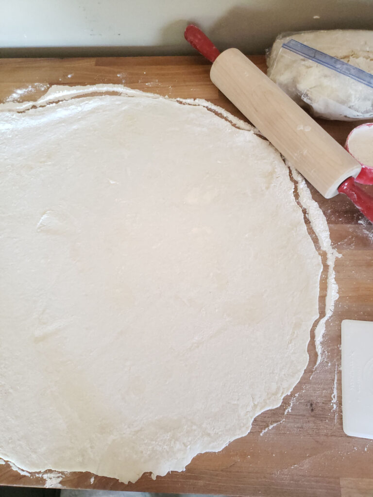 homemade pie crust rolled out on butcher block