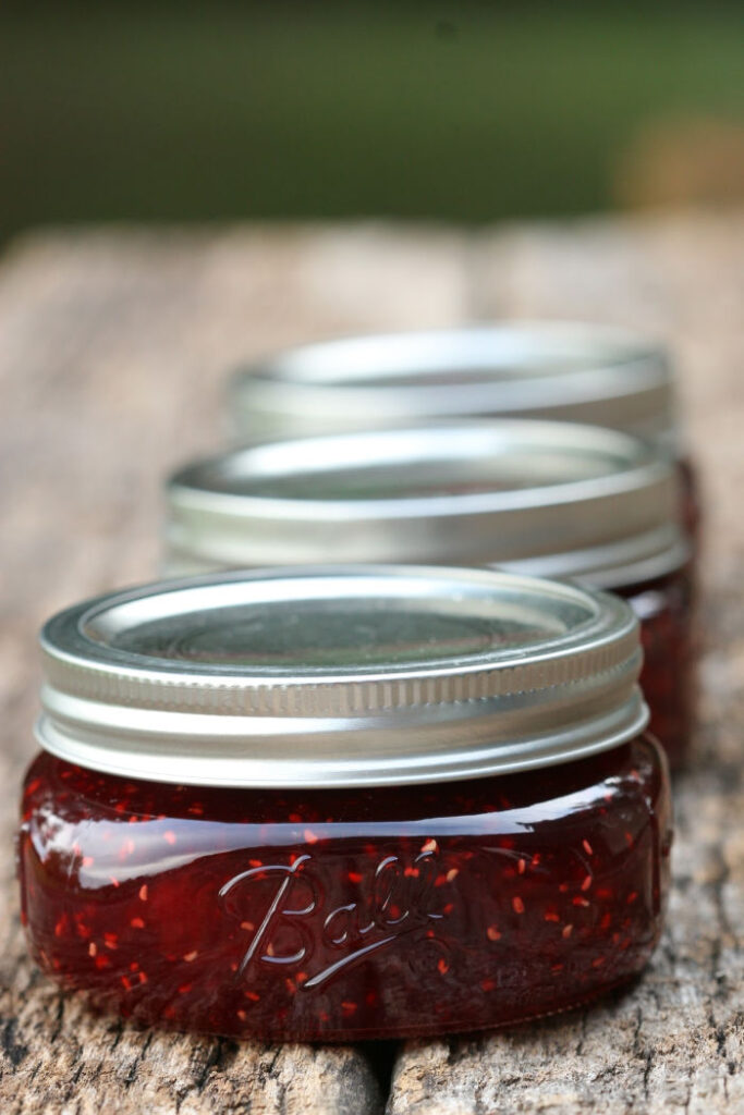 glass Mason jars of homemade raspberry jam on reclaimed wood boards