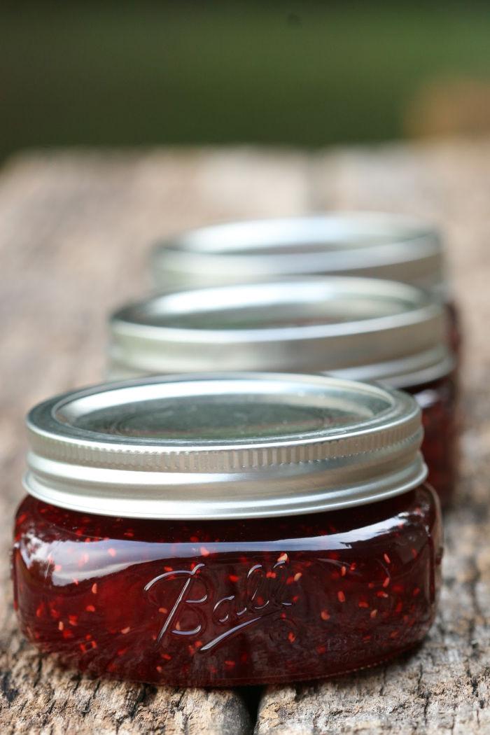 glass Mason jars of homemade raspberry jam on reclaimed wood boards.