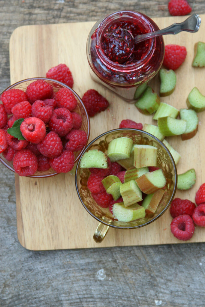 Raspberry rhubarb jam in glass jar with spoon, raspberries and rhubarb pieces in glass Depression glass tea cups