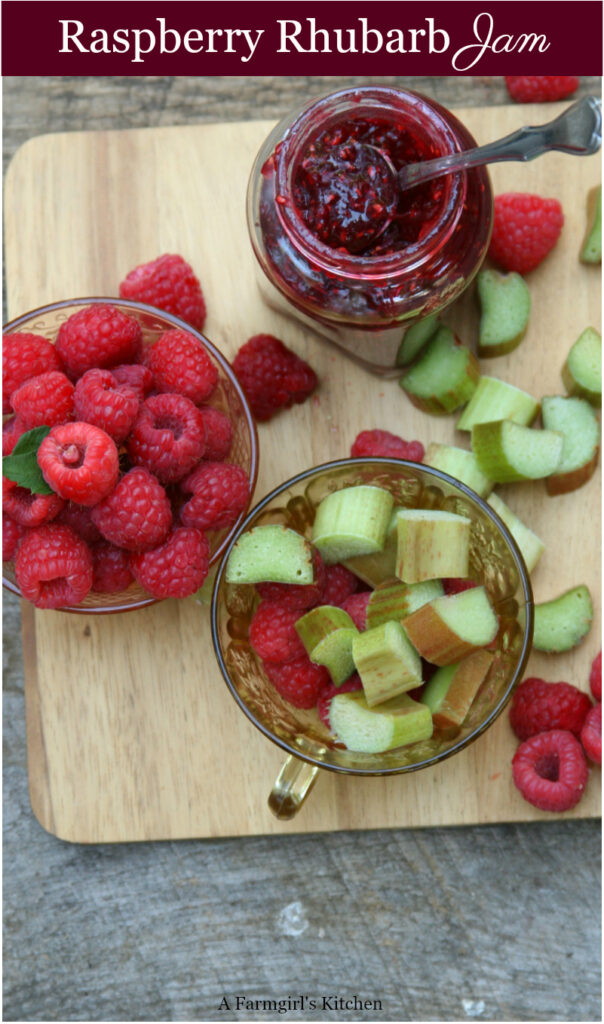 Raspberry rhubarb jam in a glass jar on wooden cutting board, spoon in jar