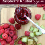 raspberry rhubarb jam in glass jar with spoon, raspberries and rhubarb pieces on wooden cutting board around jar