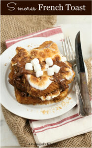stacks of S'mores French Toast on white plate with fork and knife to the right
