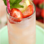 clear cylinder glass of pink lemonade with fresh strawberry and lemon slices, sprig of mint in glass.