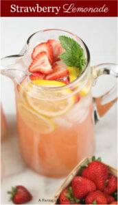 strawberry lemonade with fresh strawberries and lemon slices in pouring pitcher