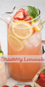 strawberry lemonade in glass pouring pitcher with fresh strawberry slices, lemon slices, and fresh mint