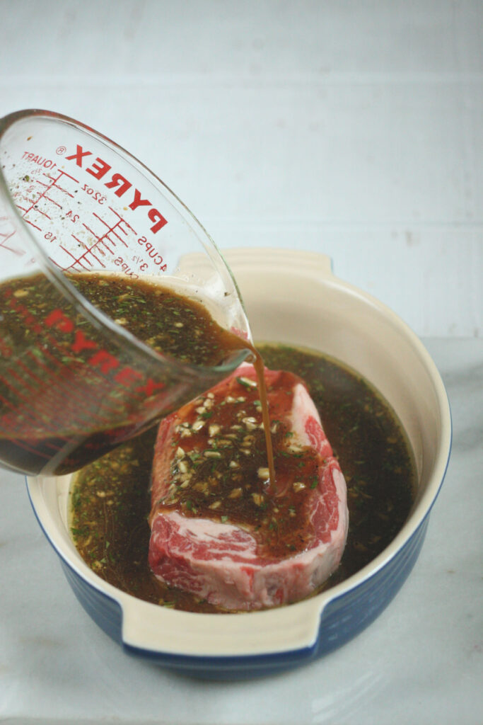steak marinade in glass measuring cup being poured over ribeye steak in ceramic baking dish