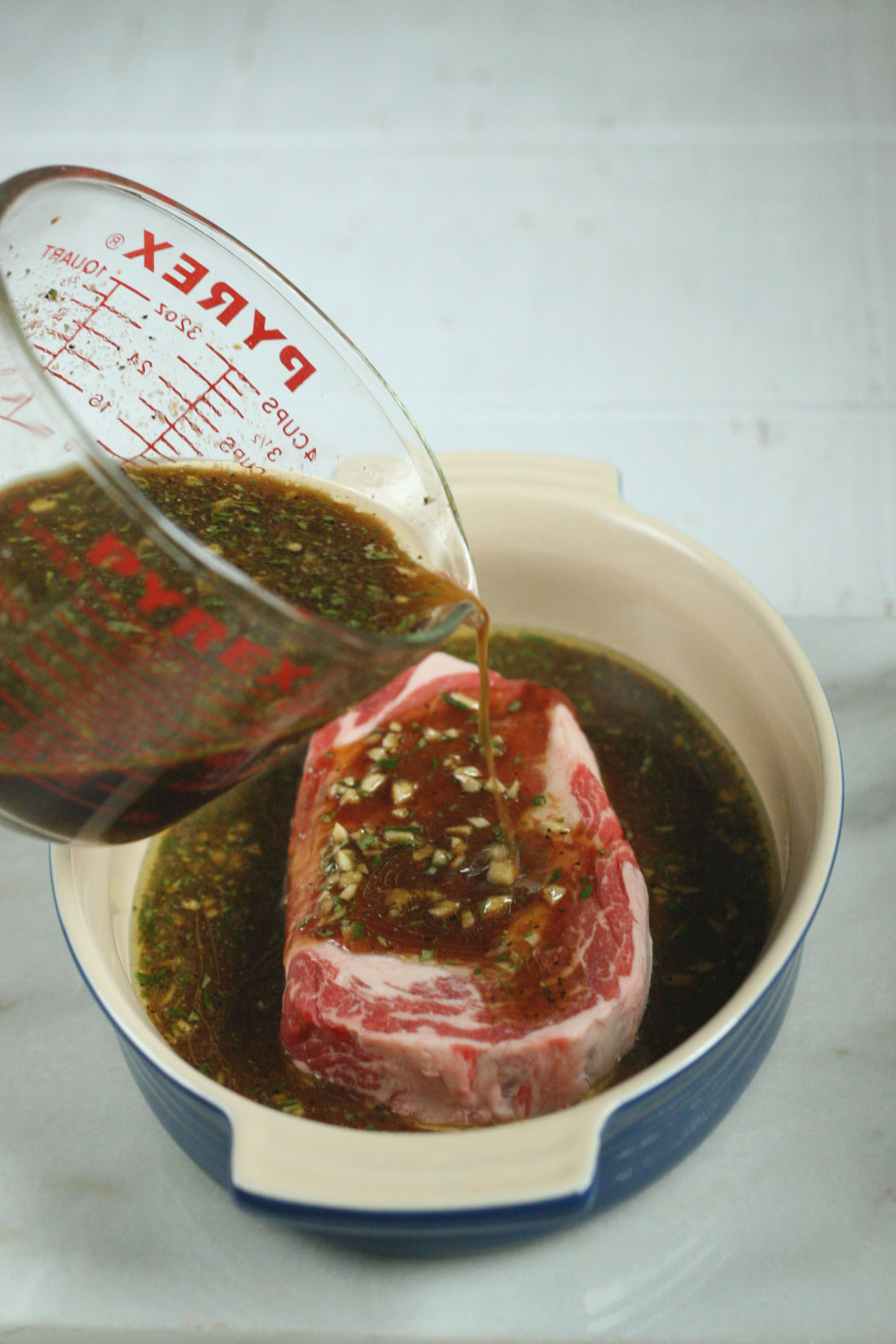 steak marinade in a glass measuring cup being poured over a steak.