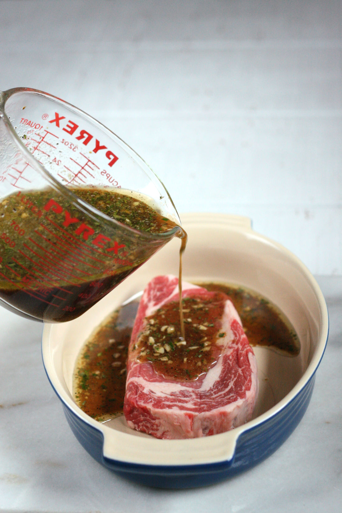 steak marinade being poured over a ribeye steak in an oval ceramic baking dish.