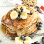 pancakes with slices of bananas and fresh blueberries stacked on white plate