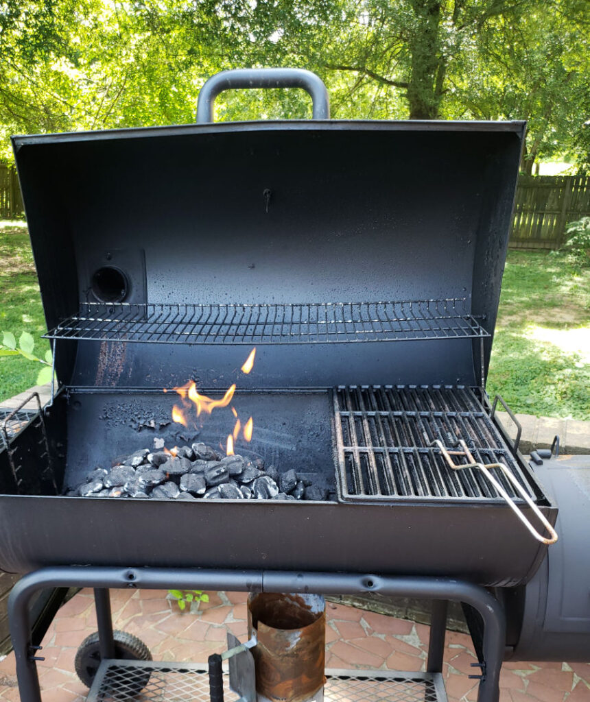 charcoal grill with lid open while charcoal burns with flames