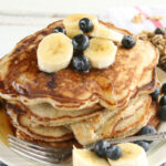 banana pancakes stacked on a white plate, topped with sliced bananas and blueberries