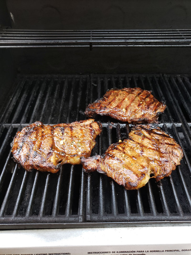 juicy steak on gas grill with browned grill marks.