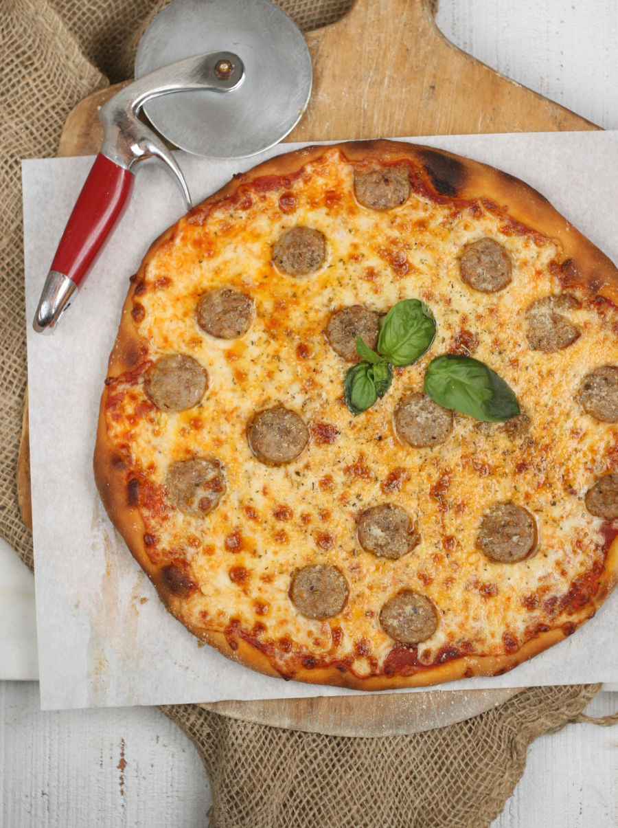 Homemade Italian style pizza with pieces of sweet sausage and basil leaves in the center.