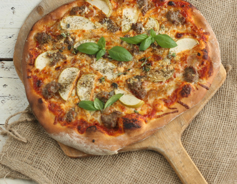 Italian-style pizza with slices of granny smith apples, cheese, and sausage.