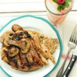 grilled chicken with mushrooms on white plate, glass of pink lemonade, fresh mint and raspberry to side