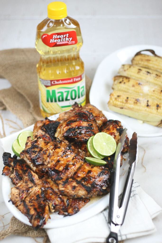 grilled chicken with tongs on white plate