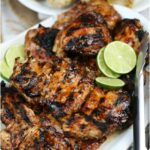 grilled chicken on white serving plate with metal tongs to right