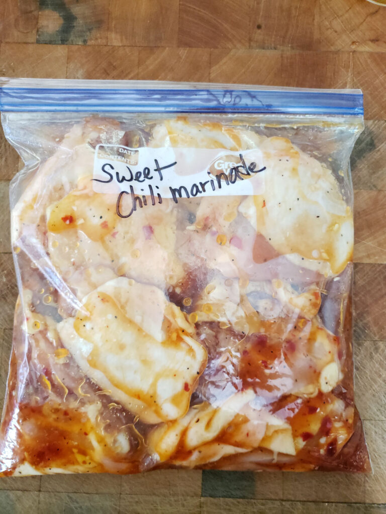 chicken marinating in gallon Ziploc bag on butcher block