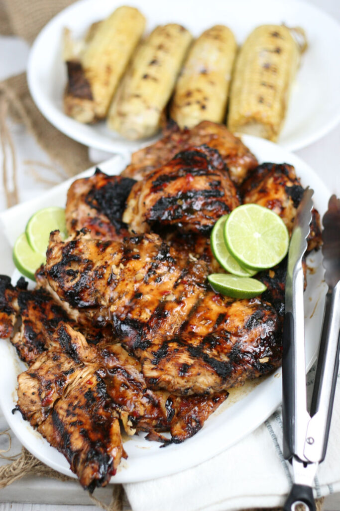grilled boneless chicken breasts on white serving plate with metal tongs