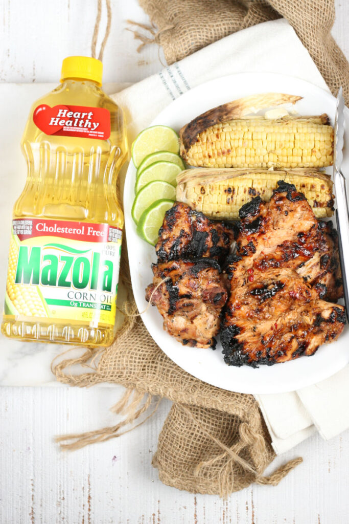 grilled chicken and corn on the cob on a white serving plate with metal tongs