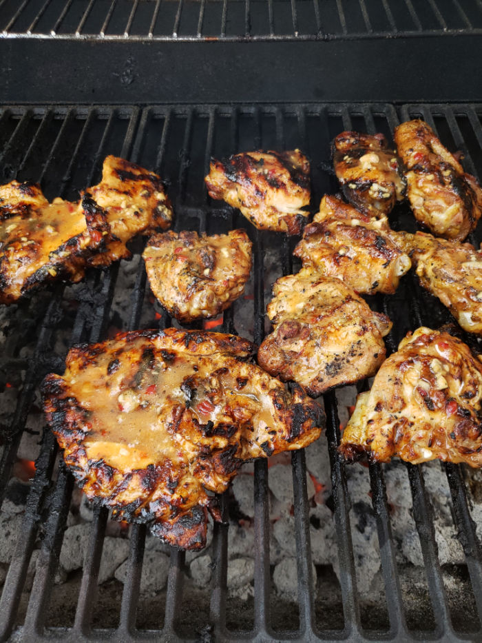 chicken pieces on charcoal grill