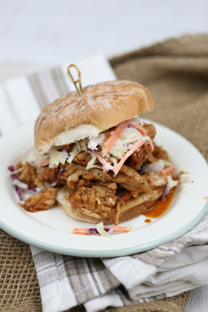 pulled pork sandwiches with homemade slaw on a white plate