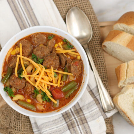 bowl of Italian sausage soup, topped with shredded yellow cheddar cheese and slices of French baguette to side of bowl