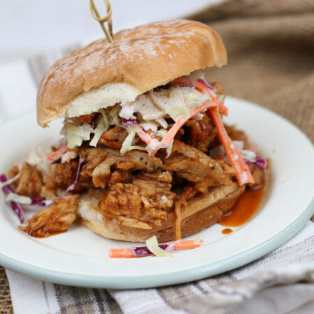 pulled pork on a soft roll topped with coleslaw
