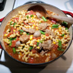 sausage soup with green beans, corn, and pasta in a red Dutch oven on kitchen stove