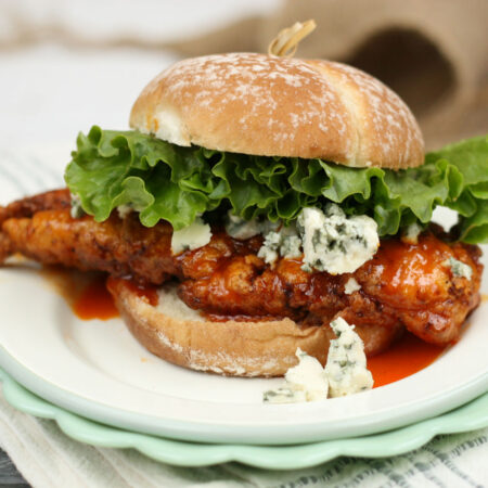honey buffalo fried chicken on a roll with chunks of blue cheese