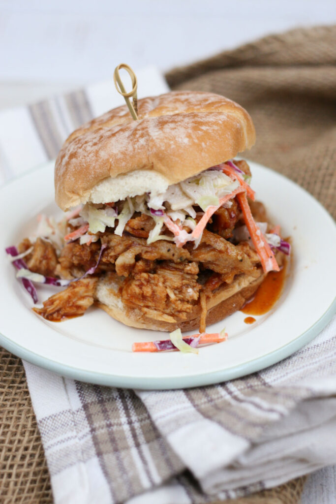 pulled pork sandwich on round roll and topped with coleslaw