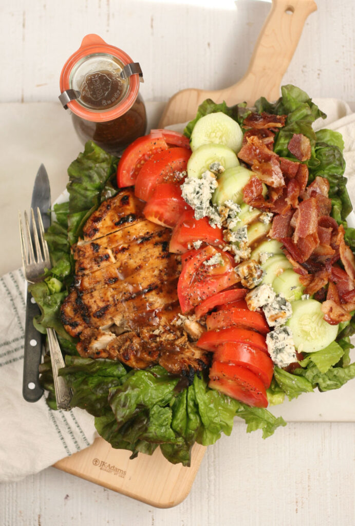 salad with chunks of grilled chicken, tomatoes, cucumbers, crispy bacon, and blue cheese