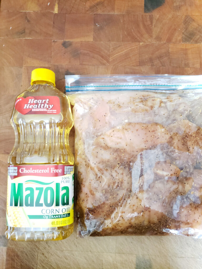 chicken breasts in a large ziploc bag marinating on butcher block